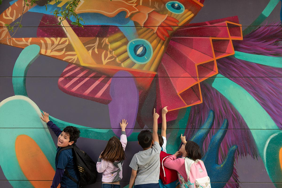 Elementary students point at mural